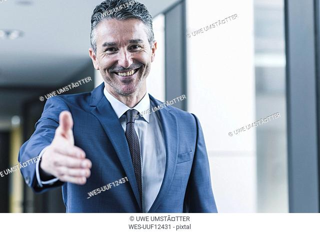 Portrait of smiling businessman about to shake hands