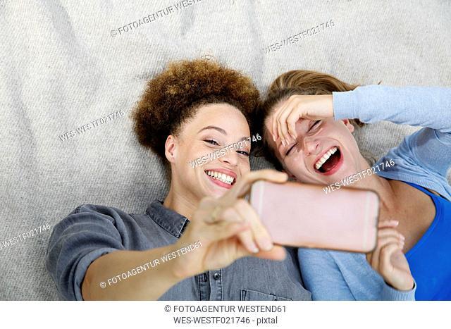 Two happy young women taking a selfie on blanket