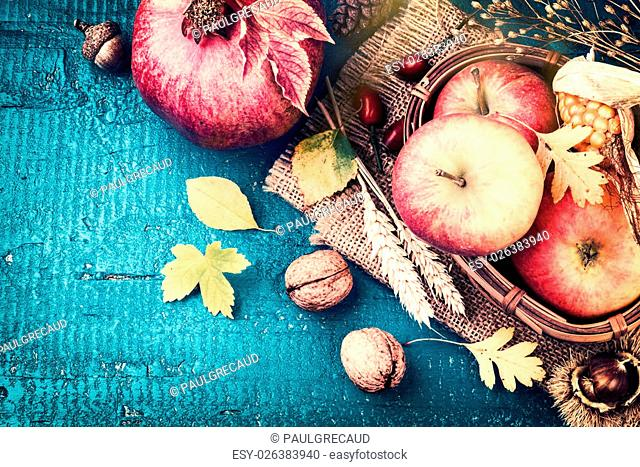 Autumn frame with pomegranate, apple and fall leaves over blue wooden background. Fall background with copy space