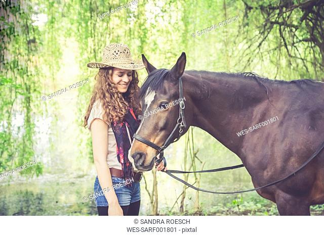 Smiling young woman with Arabian horse