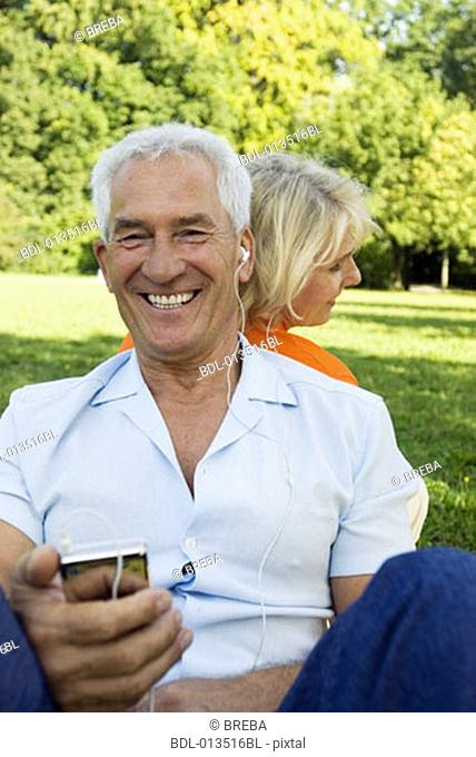 happy mature man listening to music in park with wife