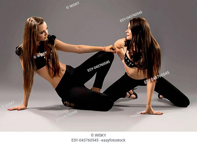 Two beautiful sexy dancers with fit bodies wearing erotic scenic clothes and high heels dancing at studio on grey background