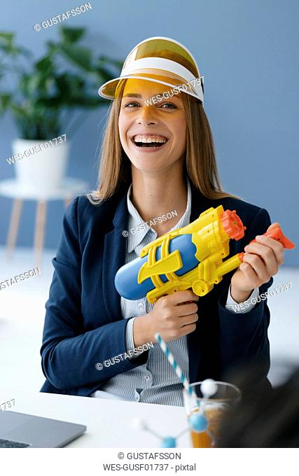 Laughing, young businesswoman, holding water gun