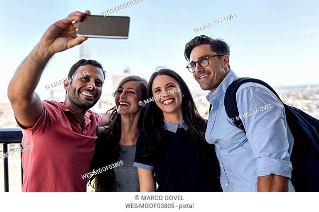 UK, London, four friends taking a selfie with city in background