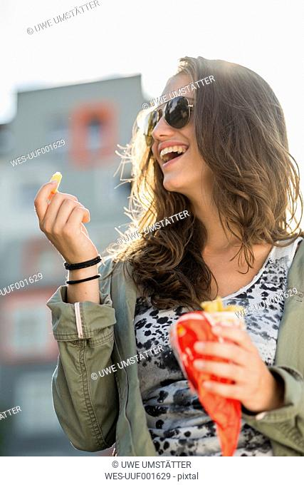 Portrait of laughing teenage girl wearing sunglasses holding paperbag of French Fries