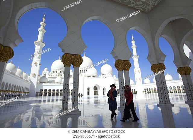 Visitors with headscarfs between the gilded columns of Sheikh Zayed Bin Sultan Al Nahyan Mosque, Abu Dhabi, United Arab Emirates, Middle East