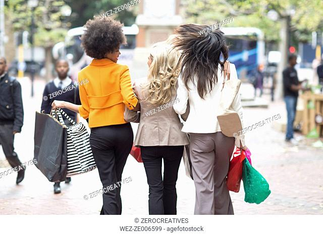 Back view of three women side by side on shopping tour