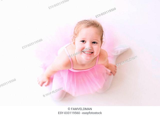 Little ballerina girl in a pink tutu. Adorable child dancing classical ballet in a white studio. Children dance. Kids performing