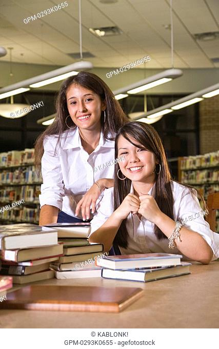 Portrait of Asian and Caucasian students in library