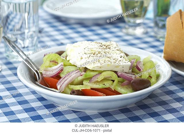 Greek salad on table glasses and plate in background
