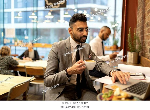Focused businessman drinking coffee and working at laptop in cafe