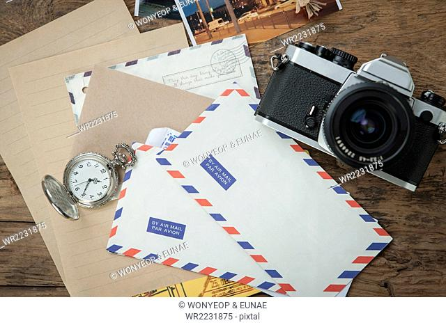 High angle of international letters placed with a camera and a pocket watch