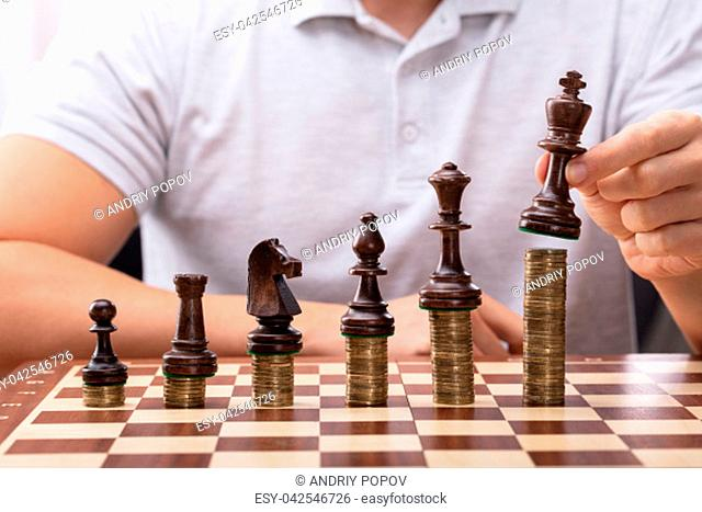 Man's Hand Placing King Chess Piece On Stacked Coins Over Chessboard