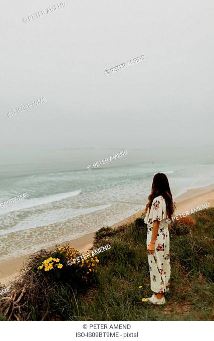 Young woman looking out at misty sea from cliff, Jalama, California, USA