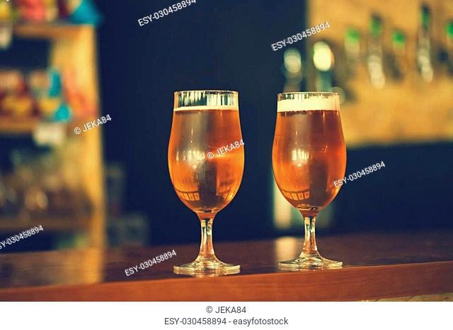 Two glasses of fresh cold light beer on a wooden bar counter in pub with free space for your text. Beautiful background of the Oktoberfest