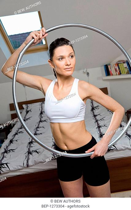 Woman doing exercises with a hoop