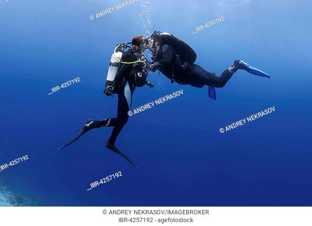 Young couple, divers kissing underwater, Indian Ocean, Maldives