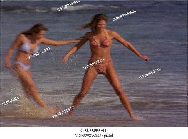 wide shot of two attractive female friends in bikinis run and frolic along the beach and in the crashing waves