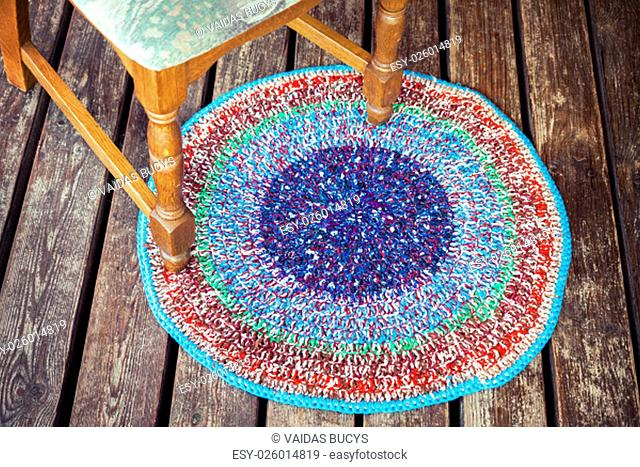 Handmade knitted colorful rug and classic style chair legs on a wooden floor