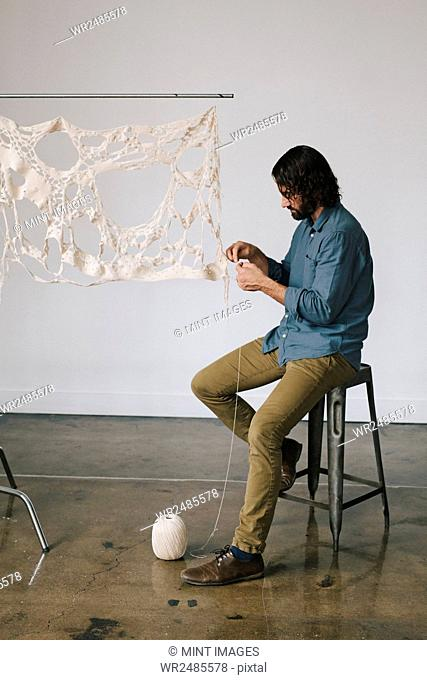 An artist working on an art piece, creating a woven and stitched object with thread