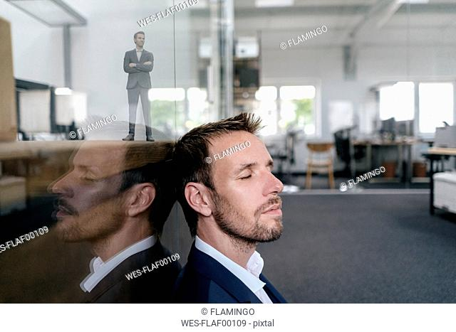 Businessman sitting in his office with his 3D portrait behind a glass pane