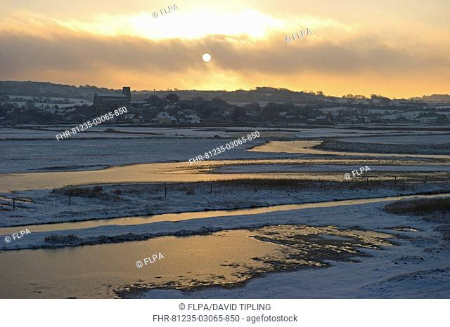 View of snow covered coastal grazing marsh habitat at sunset, Salthouse, Norfolk, England, december