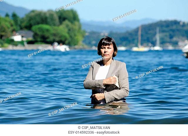 Business woman standing in the lake with her clothes on and a finacial newspaper under her arm