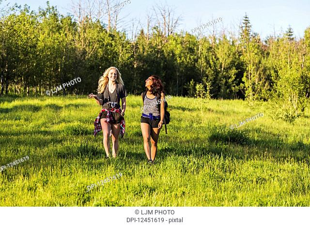 Two friends hiking and talking in a park; Edmonton, Alberta, Canada
