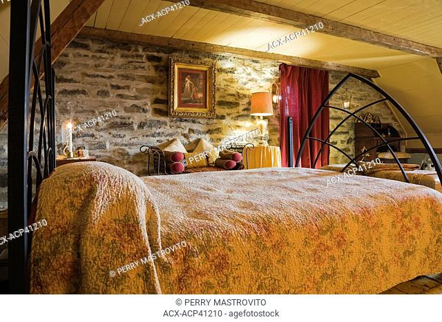 Master bedroom on the upstairs floor of an Old circa 1850 Canadiana Cottage style fieldstone residential home, Quebec, Canada