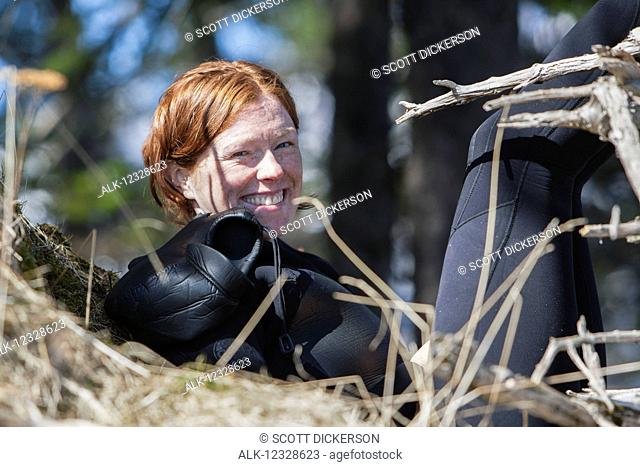 Portrait of a woman in a wetsuit sunning near the Gulf of Alaska, South-central Alaska; Alaska, United States of America