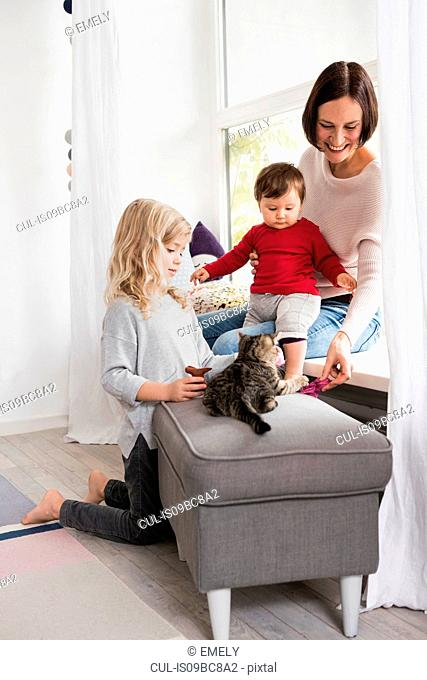 Mother and two daughters playing with pet cat