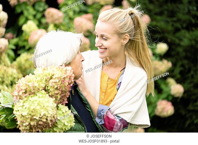 Happy young woman with her grandmother at bush in garden