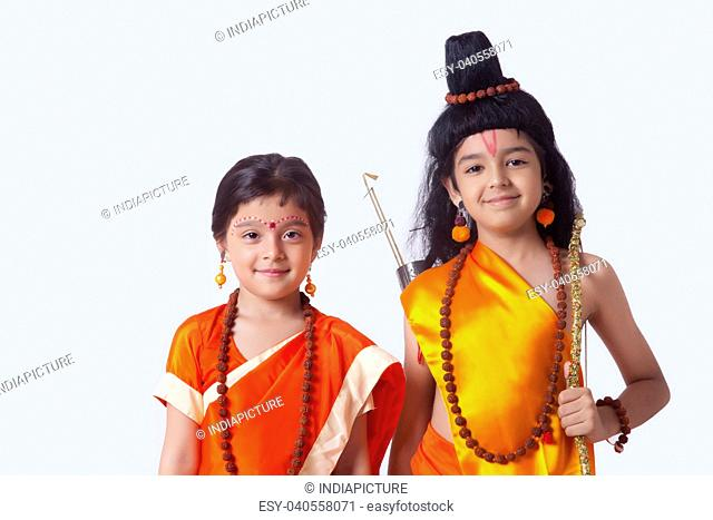 Portrait of smiling children dressed as Ram and Sita against white background