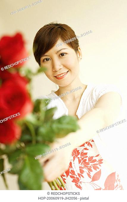 Portrait of a young woman holding a bunch of roses