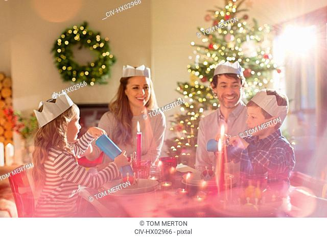 Family wearing paper crowns at Christmas dinner table
