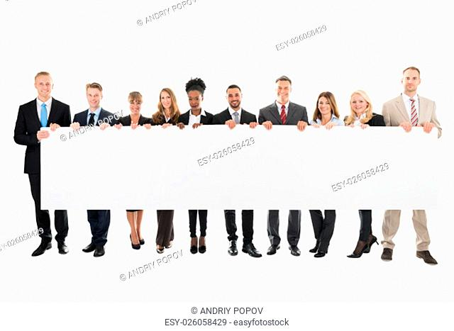 Full length rear view of doctors and nurses standing against white background
