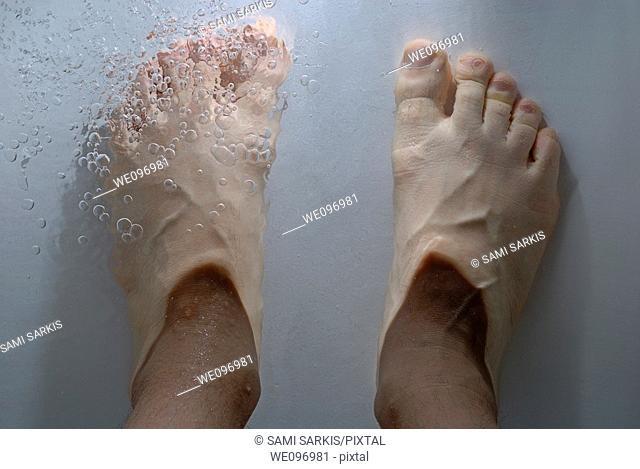 Man's feet submerged in a bathtub