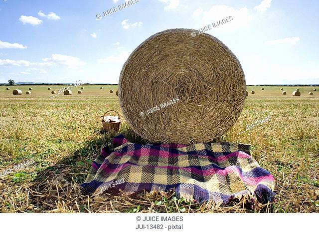 Picnic blanket in shade of hay bale in field