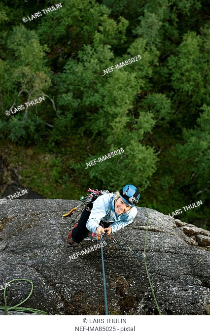 Woman climbing mountain
