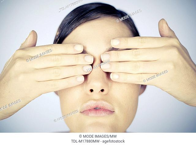 A young woman covering her eyes with her hands