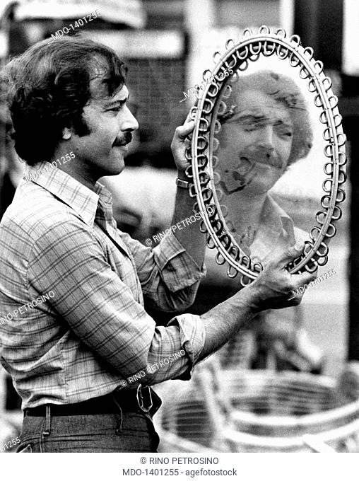 Orso Maria Guerrini looking his own face in a mirror. Portrait of Italian actor Orso Maria Guerrini at the flea market. He's looking his own face in a mirror