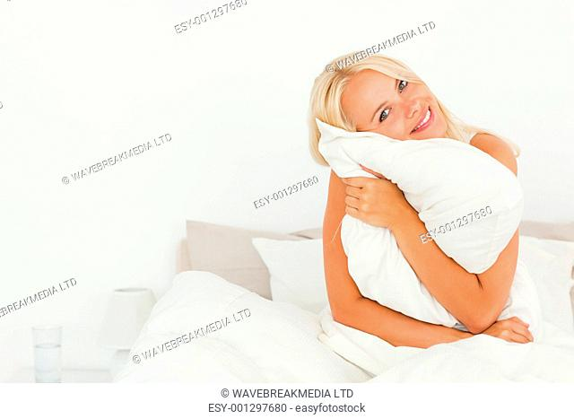 Lovely woman holding a pillow while sitting on her bed