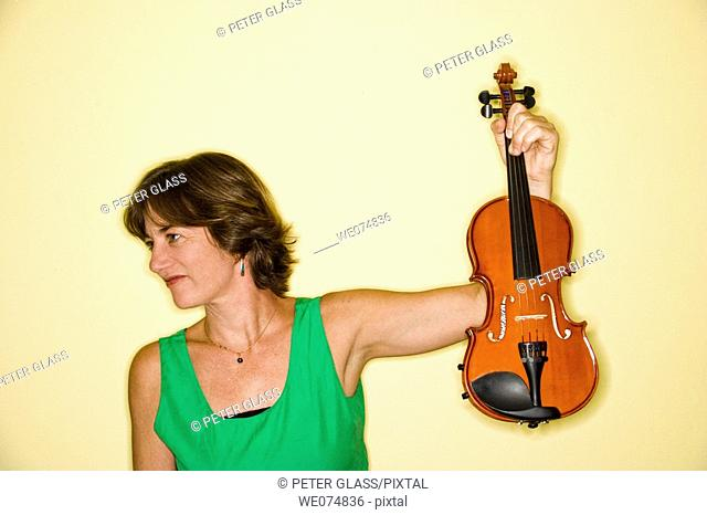 Middle age woman holding up her violin