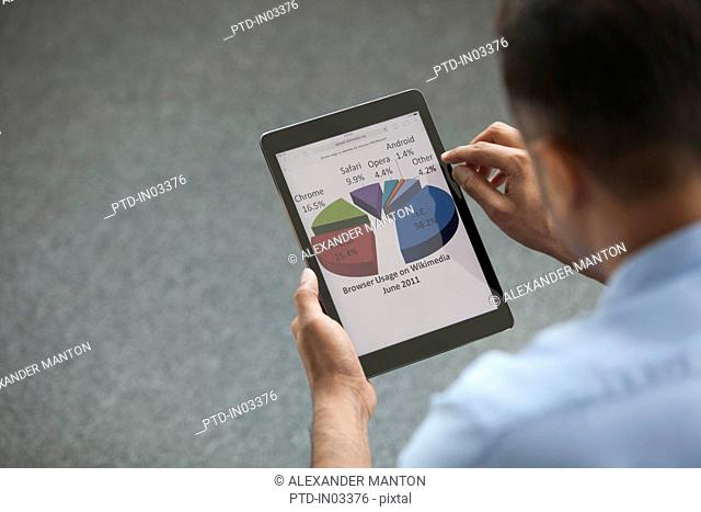 Singapore, Businessman using digital tablet with pie chart