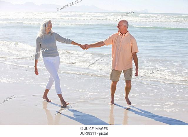 Happy senior couple holding hands and walking on sunny beach
