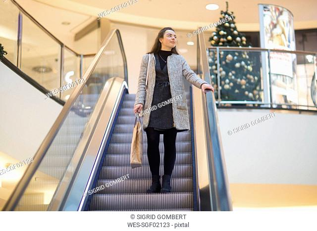 Young woman with shopping bag standing on escalator in a shopping mall at Christmas time