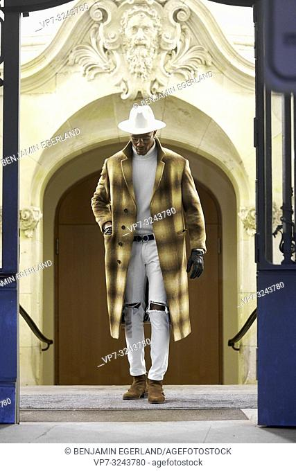 stylish wealthy man wearing expensive clothes, looking down, standing in door frame, city Munich, Germany
