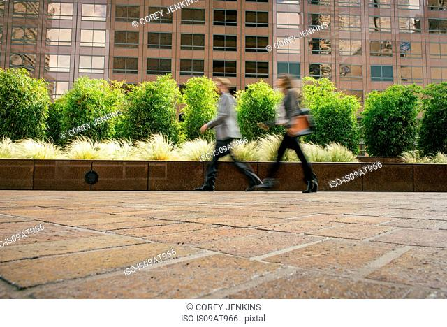 Businessman and woman walking in a hurry outside office buildings