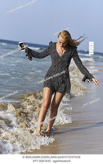 Greece, Crete, Malia, woman with smart phone walking on beach between waves