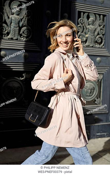 Blond woman running with smartphone